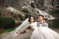 Όμορφο γαμήλιο photosession Ο νεόνυμφος περιβάλλει τη νέα νύφη του, στην ακτή της λίμνης Morskie Oko r στοκ εικόνα με δικαίωμα ελεύθερης χρήσης