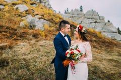 Όμορφο γαμήλιο ζεύγος στο ειδυλλιακό ποιμενικό τοπίο με τους βράχους και φράκτης ως backround Νεόνυμφος στο μοντέρνο μπλε κοστούμ Στοκ εικόνες με δικαίωμα ελεύθερης χρήσης