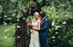 Όμορφο γαμήλιο ζεύγος στο πάρκο Φιλί και αγκάλιασμα μεταξύ τους Στοκ Φωτογραφίες