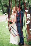 Όμορφο γαμήλιο ζεύγος στο πάρκο Φιλί και αγκάλιασμα μεταξύ τους Στοκ φωτογραφία με δικαίωμα ελεύθερης χρήσης