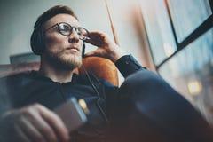 Όμορφο γενειοφόρο άτομο πορτρέτου που φορά τα γυαλιά, ακουστικά που ακούνε τη μουσική στο σύγχρονο σπίτι Συνεδρίαση τύπων στην εκ Στοκ εικόνα με δικαίωμα ελεύθερης χρήσης