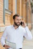 Όμορφο γενειοφόρο άτομο που κουβεντιάζει σε κινητό του Στοκ Εικόνες