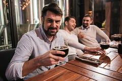 Όμορφο γενειοφόρο άτομο που κρατά ένα γυαλί με την μπύρα Στοκ Εικόνες