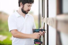 Όμορφο γενειοφόρο άτομο που τρυπά τον ξύλινο τοίχο σπιτιών με τρυπάνι Στοκ Εικόνες