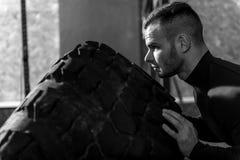 Όμορφο γενειοφόρο άτομο που ωθεί τη γιγαντιαία ρόδα Στοκ φωτογραφία με δικαίωμα ελεύθερης χρήσης