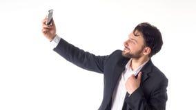 Όμορφο γενειοφόρο νέο επιχειρησιακό άτομο που παίρνει selfie το χαμόγελο πορτρέτο που απομονώνεται πέρα από το άσπρο υπόβαθρο στο Στοκ Εικόνα