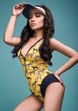 Όμορφο γοητευτικό ασιατικό κορίτσι στο ζωηρόχρωμο μαγιό σε ένα φωτεινό υπόβαθρο Στοκ εικόνα με δικαίωμα ελεύθερης χρήσης