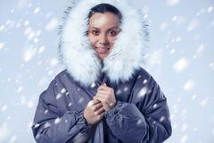 Όμορφο γοητευτικό ισπανικό κορίτσι στο μπλε παλτό με το μειωμένο χιόνι Στοκ Εικόνα