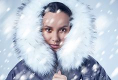 Όμορφο γοητευτικό ισπανικό κορίτσι στο μπλε παλτό με το μειωμένο χιόνι Στοκ Φωτογραφίες