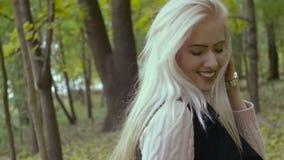 Όμορφο γοητευτικό νέο κορίτσι που περπατά στην τοποθέτηση φλερτ πάρκων φθινοπώρου για τη κάμερα Χαμόγελο απόθεμα βίντεο