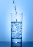 Όμορφο γυαλί με το νερό σε ένα μπλε υπόβαθρο Στοκ φωτογραφία με δικαίωμα ελεύθερης χρήσης