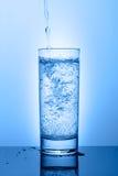 Όμορφο γυαλί με το νερό σε ένα μπλε υπόβαθρο Στοκ Εικόνες