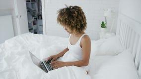 Όμορφο γυναικών στο κρεβάτι με το lap-top απόθεμα βίντεο