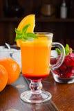 Όμορφο γλυκό κοκτέιλ με την πορτοκαλιούς φράουλα και τον πάγο μεντών Στοκ Φωτογραφία