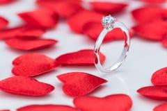 Όμορφο δαχτυλίδι διαμαντιών στον άσπρο πίνακα με τις μικρές αισθητές κόκκινο καρδιές Στοκ εικόνα με δικαίωμα ελεύθερης χρήσης