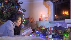 Όμορφο διαβασμένο brunette βιβλίο που βάζει κοντά στο χριστουγεννιάτικο δέντρο και την εστία φιλμ μικρού μήκους