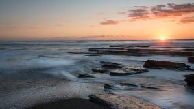 Όμορφο δραματικό ηλιοβασίλεμα πέρα από μια δύσκολη ακτή Στοκ Εικόνες