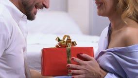 Όμορφο δόσιμο γυναικών παρόν στο φίλο, ευχάριστη έκπληξη κατά τη ρομαντική ημερομηνία απόθεμα βίντεο