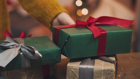 Όμορφο δώρο στα χέρια των ατόμων Δώρο του νέου έτους με μια κόκκινη κορδέλλα, έλατο στον πίνακα Το άτομο το έκανε ο ίδιος και είν απόθεμα βίντεο