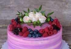 Όμορφο εγχώριο κέικ με τη ρόδινη και πορφυρή κρέμα, που διακοσμείται με τα άσπρα τριαντάφυλλα και τα μούρα του Blackberry, βακκίν Στοκ Εικόνες
