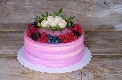 Όμορφο εγχώριο κέικ με τη ρόδινη και πορφυρή κρέμα, που διακοσμείται με τα άσπρα τριαντάφυλλα και τα μούρα του Blackberry, βακκίν Στοκ φωτογραφία με δικαίωμα ελεύθερης χρήσης