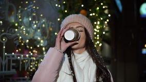 Όμορφο ελκυστικό κορίτσι που στέκεται δίπλα σε μια βιτρίνα που διακοσμείται με τα φω'τα Χριστουγέννων και που εξετάζει τη κάμερα  απόθεμα βίντεο