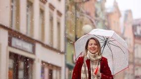 Όμορφο ενήλικο κορίτσι στο κόκκινο παλτό και μαντίλι με την ομπρέλα απόθεμα βίντεο