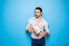 Όμορφο ενήλικο άτομο στο μπλε υπόβαθρο με το δώρο Χριστουγέννων Στοκ Φωτογραφίες