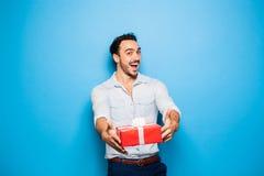Όμορφο ενήλικο άτομο στο μπλε υπόβαθρο με το δώρο Χριστουγέννων Στοκ Εικόνες