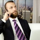 Όμορφο επιχειρησιακό άτομο με την εργασία γενειάδων στην αρχή στο τηλέφωνο lap-top και κυττάρων Στοκ Φωτογραφία