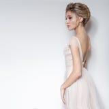 Όμορφο λεπτό προκλητικό κορίτσι νυφών στο μαλακό ρόδινο γαμήλιο φόρεμα skazachno με μια περικοπή στο στήθος και πίσω με το makeup Στοκ Εικόνες