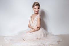 Όμορφο λεπτό προκλητικό κορίτσι νυφών στο μαλακό ρόδινο γαμήλιο φόρεμα skazachno με μια περικοπή στο στήθος και πίσω με το makeup Στοκ Φωτογραφία