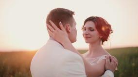 Όμορφο ερωτευμένο φιλί ζευγών στη φύση στη ημέρα γάμου τους στο καλοκαίρι Θαυμάσιο ηλιοβασίλεμα στην επαρχία απόθεμα βίντεο