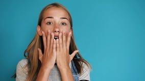 Όμορφο ευτυχές έκπληκτο κορίτσι με τις θετικές συγκινήσεις πέρα από το μπλε υπόβαθρο Πορτρέτο του χαριτωμένου έκπληκτου και συγκλ απόθεμα βίντεο