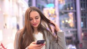 Όμορφο ευτυχές κορίτσι με μακρυμάλλη γράφοντας ένα μήνυμα στο smartphone που στέκεται στη λεωφόρο σε αργή κίνηση 4 Κ φιλμ μικρού μήκους