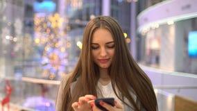 Όμορφο ευτυχές κορίτσι με μακρυμάλλη γράφοντας ένα μήνυμα στο smartphone που στέκεται στη λεωφόρο σε αργή κίνηση χρήση γυναικών φιλμ μικρού μήκους
