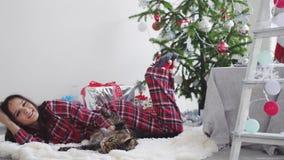 Όμορφο ευτυχές κορίτσι που βρίσκεται εκτός από fir-tree Χριστουγέννων σε μια κουβέρτα στις πυτζάμες που παίζουν με τη γάτα του Μα φιλμ μικρού μήκους