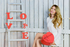Όμορφο ευτυχές κορίτσι που κρατά μια καρδιά giftbox Στοκ Φωτογραφίες