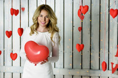 Όμορφο ευτυχές κορίτσι που κρατά μια καρδιά giftbox Στοκ Φωτογραφία