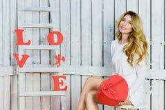 Όμορφο ευτυχές κορίτσι που κρατά μια καρδιά giftbox Στοκ Εικόνες