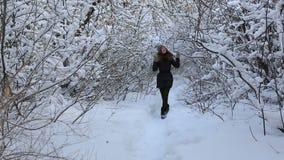 Όμορφο ευτυχές κορίτσι που περπατά στο χειμερινό πάρκο και απόθεμα βίντεο