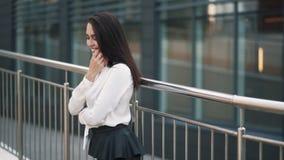 Όμορφο ευτυχές κορίτσι στην άσπρη μπλούζα, μαύρη τοποθέτηση φουστών στη κάμερα, σε αργή κίνηση απόθεμα βίντεο