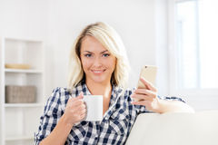 Όμορφο ευτυχές κορίτσι στον καναπέ με ένα φλυτζάνι του τσαγιού Στοκ εικόνα με δικαίωμα ελεύθερης χρήσης