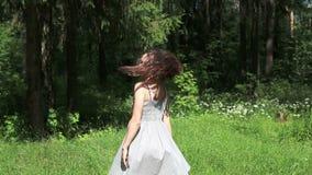 Όμορφο ευτυχές κορίτσι στους γκρίζους χορούς φορεμάτων φιλμ μικρού μήκους