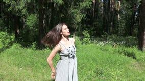 Όμορφο ευτυχές κορίτσι στους χορούς φορεμάτων φιλμ μικρού μήκους