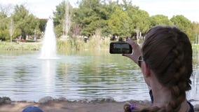 Όμορφο ευτυχές νέο κορίτσι που κάνει τη φωτογραφία που χρησιμοποιεί το smartphone στο φως ήλιων απόθεμα βίντεο