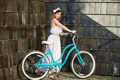Όμορφο ευτυχές οδηγώντας ποδήλατο γυναικών στην πόλη στοκ φωτογραφία
