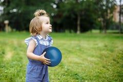 Όμορφο ευτυχές παιχνίδι μικρών κοριτσιών με μια σφαίρα σε ένα πράσινο λιβάδι στη φύση στο πάρκο Στοκ φωτογραφία με δικαίωμα ελεύθερης χρήσης