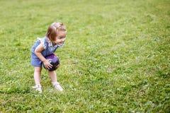 Όμορφο ευτυχές παιχνίδι μικρών κοριτσιών με μια σφαίρα σε ένα πράσινο λιβάδι στη φύση στο πάρκο Στοκ Εικόνα