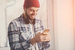 Όμορφο ευτυχές hipster που χρησιμοποιεί το έξυπνο τηλέφωνο στο παράθυρο στοκ εικόνες